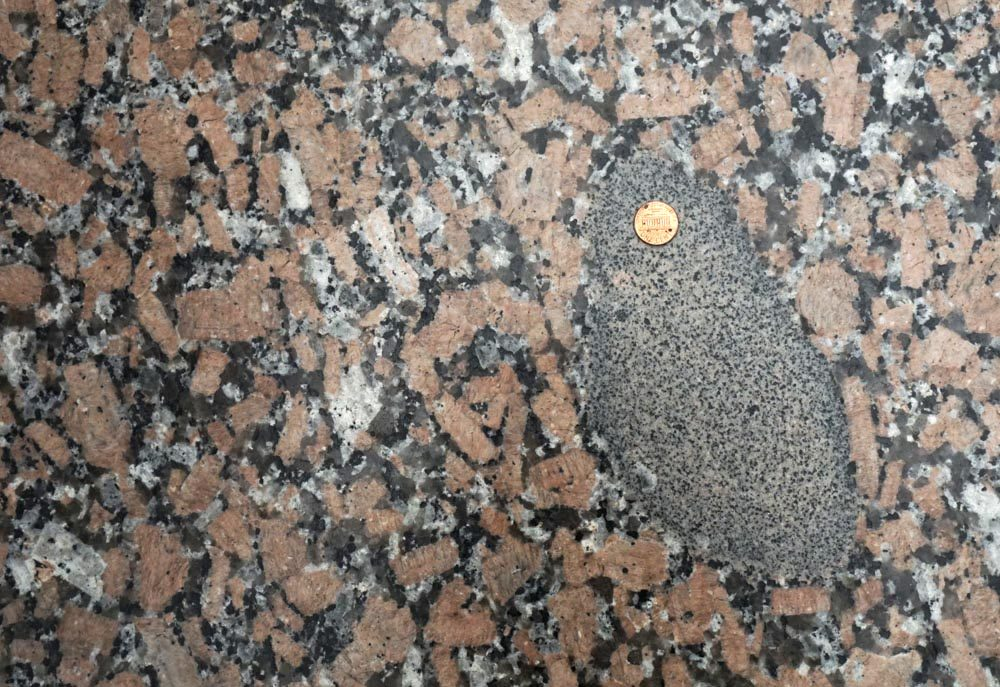 This image shows the principle of inclusions. The dark colored inclusion is older than the surrounding granite.